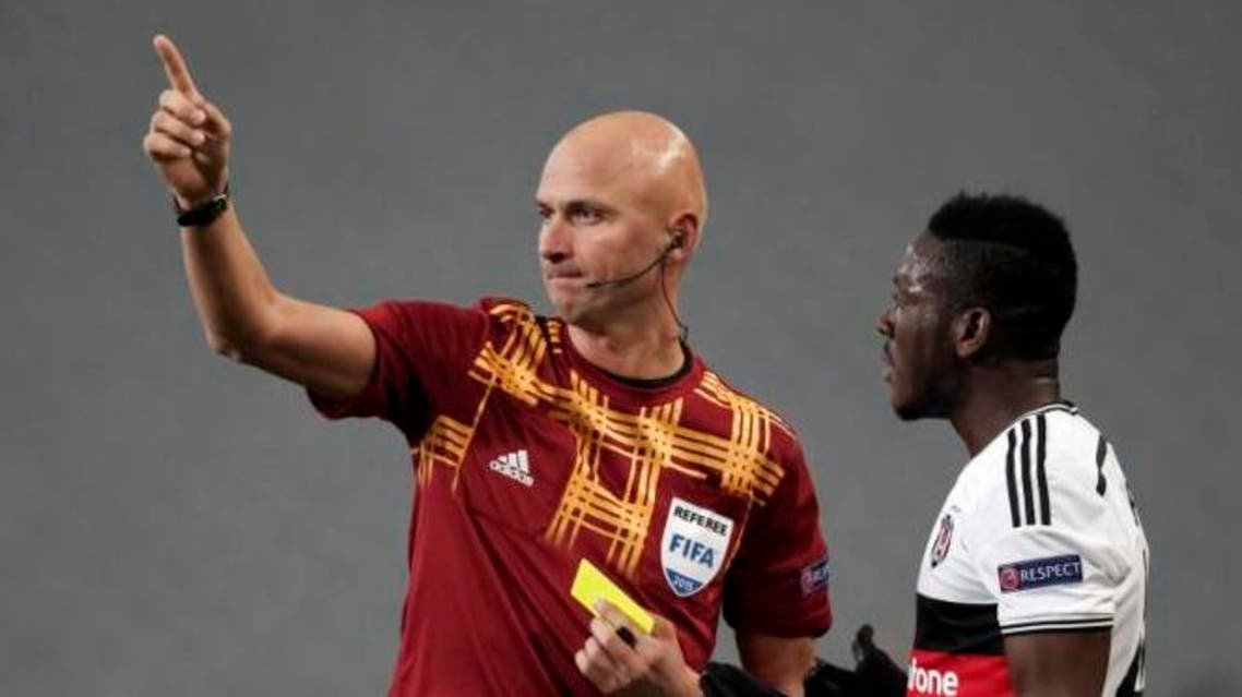 Daniel Opare of Besiktas (R) argues with referee Sergei Karasev of Russia during the Europa League round of 16 second leg soccer match against Club Brugge in Istanbul March 19, 2015. (Reuters)