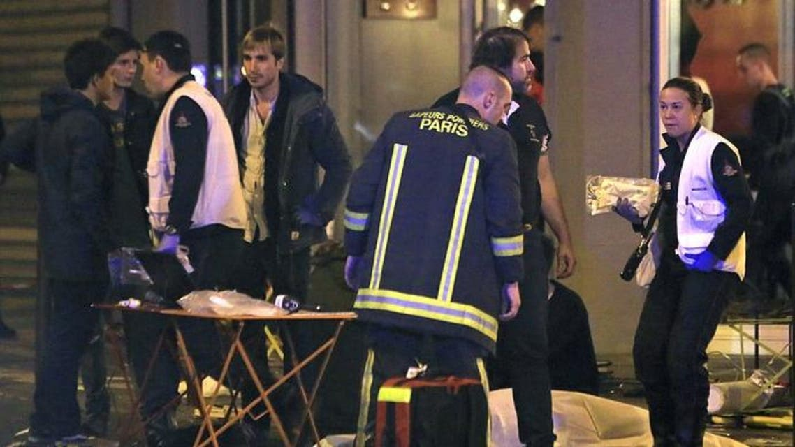Rescue workers are shown at the scene as victims lay on the pavement outside a Paris restaurant, Nov. 13, 2015.