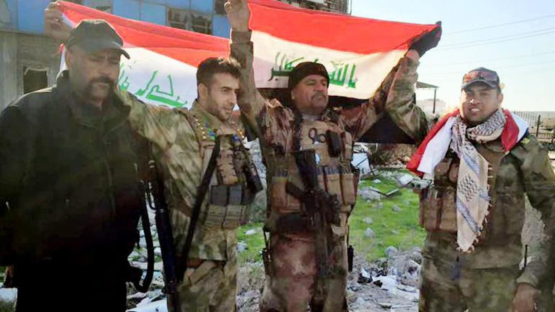 Iraqi soldiers hold national flags in the government complex in central Ramadi, 70 miles (115 kilometers) west of Baghdad, Iraq, Monday, Dec. 28, 2015. (AP)