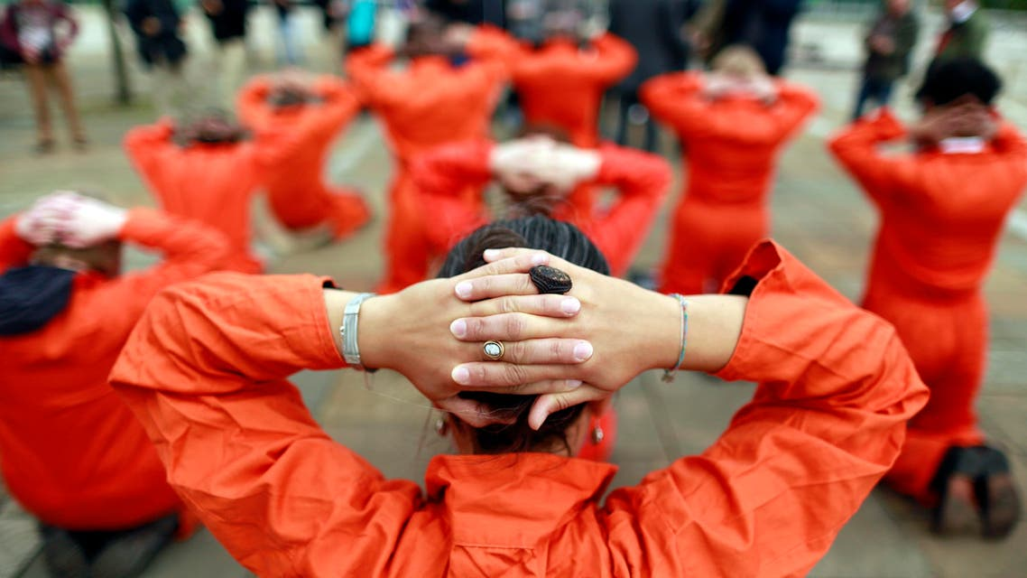 Activists from Amnesty International dressed as Guantanamo Bay detainees take part in a photo call in front of the Waterfront Hall in Belfast June 16, 2013. (Reuters)
