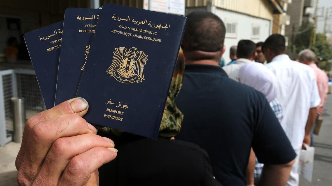 In this Friday, Sept. 11, 2015 photo, a Syrian man holds his family's passports as he lines up with other Syrians to apply for asylum visas, outside the German embassy, in Rabieh, north Beirut, Lebanon. (File photo: AP)
