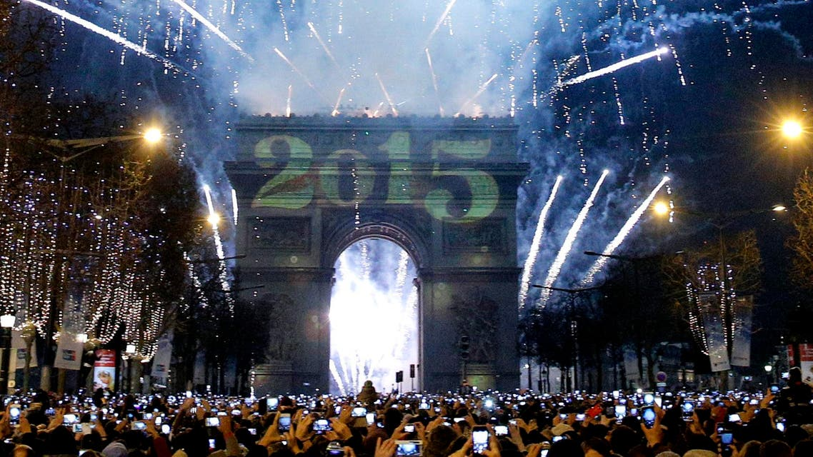 Revelers photograph fireworks over the Arc de Triomphe as they celebrate the New Year's Eve on the Champs Elysees avenue in Paris, France, Thursday, Jan. 1, 2015. (AP)