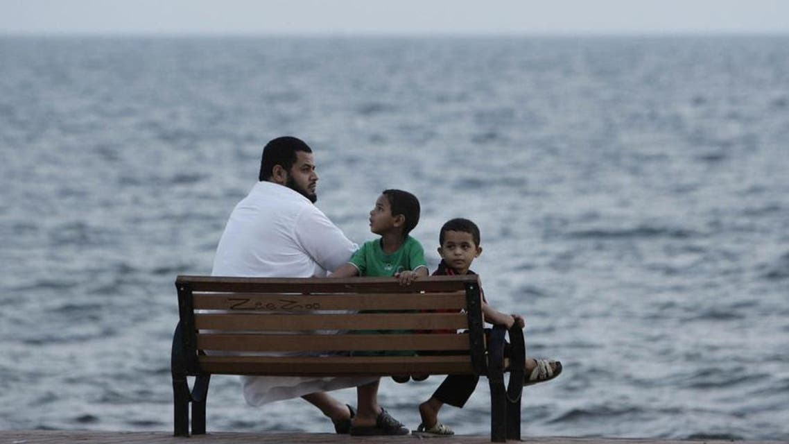 Illustrative photo: A man and his children sit on a bench next to the Red Sea in Jizan October 6, 2010. (Reuters)