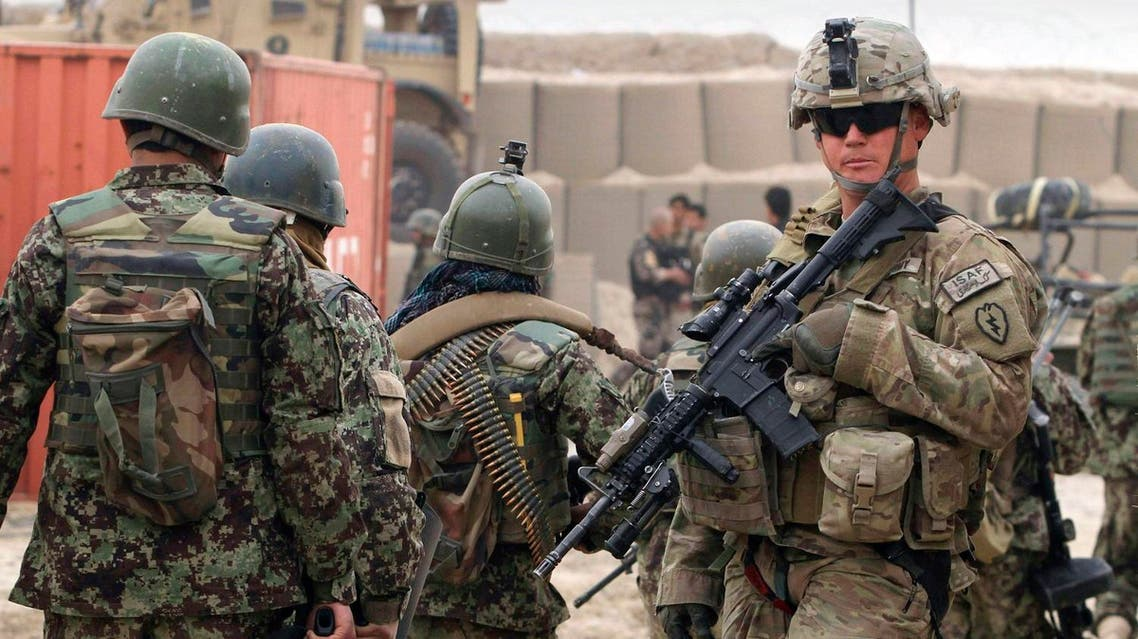 In this Sunday, March 11, 2012 photo, Afghan soldiers, left, walk past a U.S. Army soldier outside of a military base in Panjwai, Kandahar province south of Kabul, Afghanistan. (AP)