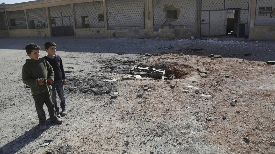 Boys stand at a ground damaged by what activists said were air strikes carried out yesterday by the Russian air force at a school in Jerjnaz town in Idlib. (Reuters)