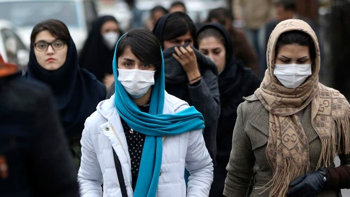 Iranian women wear masks for protection against air pollution as they make their way on a street in northern Tehran. (AP)