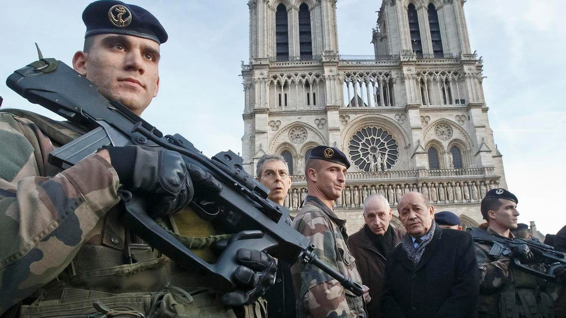 France's Defense Minister Jean-Yves Le Drian, 2nd right, talks to soldiers at the Notre Dame cathedral in Paris. (AP)