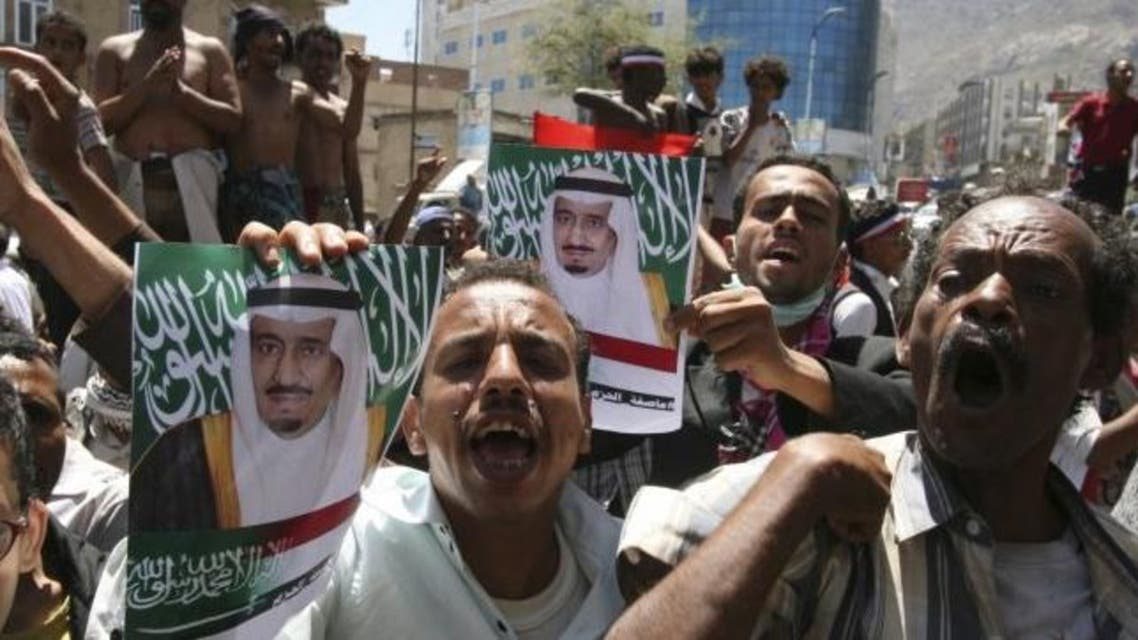 Anti-Houthi protesters hold posters of Saudi King Salman to show their support for Saudi-led airstrikes in Yemen (Reuters)