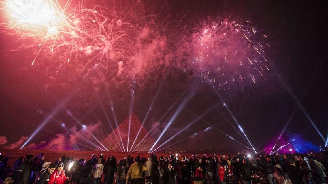 Egyptians celebrate the New Year in front of the pyramids near the Egyptian capital Cairo on January 1, 2016. AFP PHOTO / KHALED DESOUKI