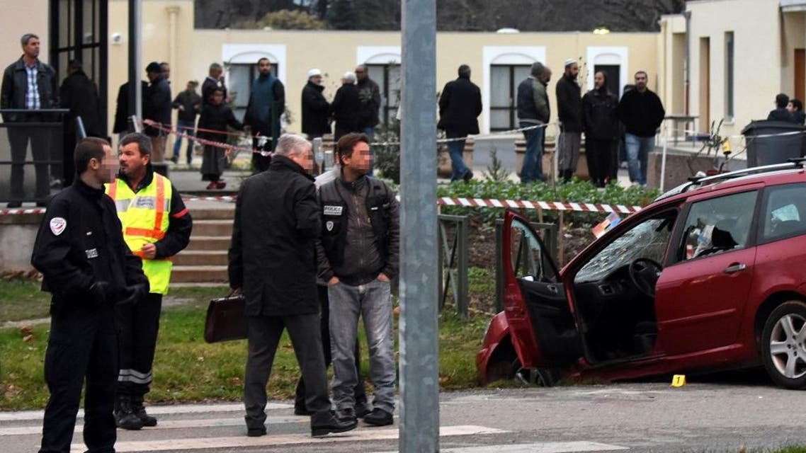 French police and criminal investigators stand next to a car in front of the mosque of Valence, southeastern France, on January 1, 2016, after a soldier guarding the mosque shot and wounded a driver who rammed him with the car. (AFP)