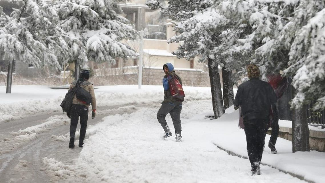 Syrian workers carry their belonging as they walk on the snow in Aley, Lebanon, January 1, 2016 | Reuters