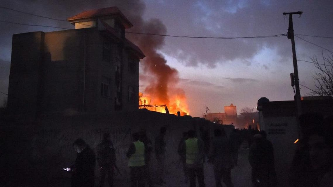 Security personnel and bystanders look on as flames and smoke rise at the site of a suicide car bomb attack at a French restaurant- Le Jardin in Kabul on January 1, 2016. A Taliban suicide car bomber raided a French restaurant popular with foreigners in Kabul, in a New Year's day attack that marks the latest in a series of brazen insurgent assaults.There was no immediate confirmation of casualties from the attack on Le Jardin, an Afghan-owned eatery, which caused a piercingly loud explosion and left a building engulfed in flames. AFP PHOTO/Wakil Kohsar