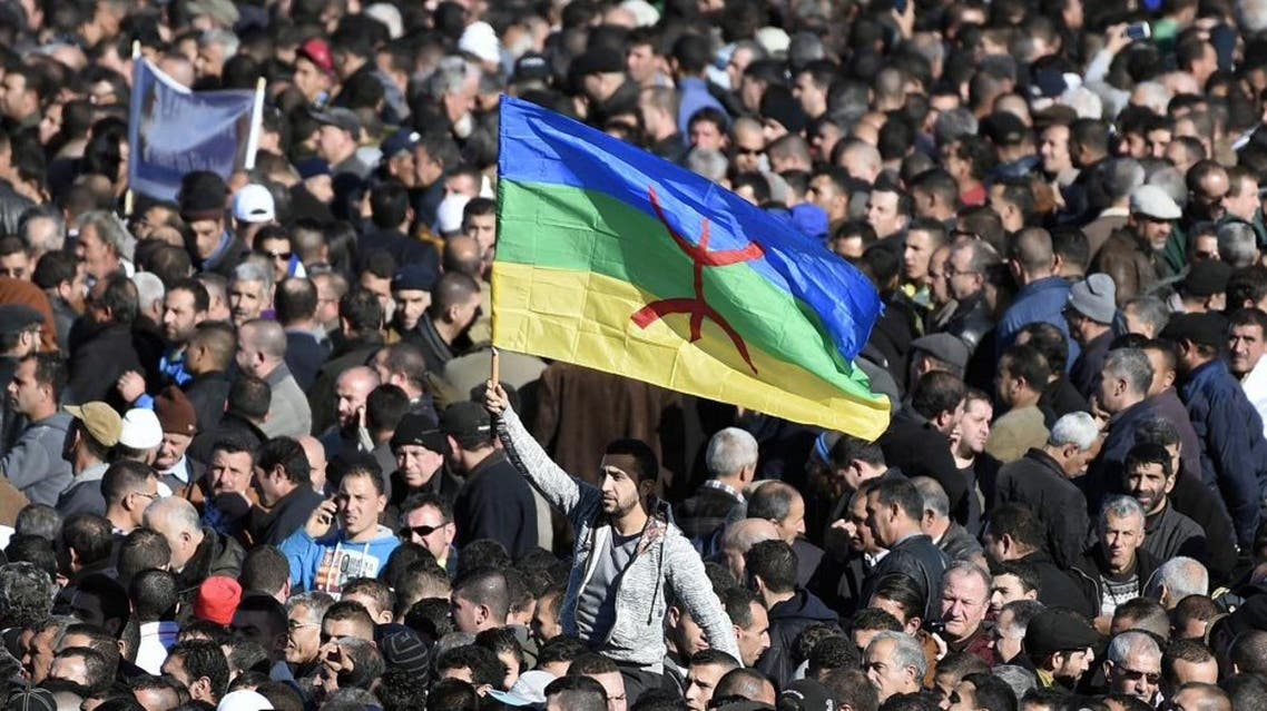 A man waves the Amazigh flag as thousands of mourners attend the funeral procession and burial of Hocine Ait-Ahmed, one of the fathers of Algeria's struggle for independence and a key opposition figure, in the Algerian village of Ait Ahmed on January 1, 2016. Ait-Ahmed's remains arrived in Algiers from Switzerland, where he died at the age of 89, for a state funeral the previous day before being transferred to his home village for his burial. The Amazighs, or Berbers, are the ethnicity indigenous to North Africa west of the Nile Valley. AFP PHOTO / FAROUK BATICHE