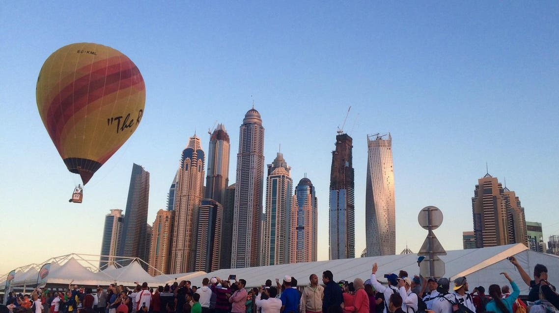 Spectators watch hot air balloons participating in the World Air Games as one soars past the Dubai Marina in Dubai, United Arab Emirates. (AP)