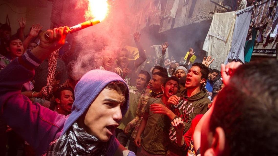 In this Friday, April 24, 2015 file photo, an Egyptian youth carries a lit flare as supporters of the Muslim Brotherhood gather in the El-Mataria neighborhood of Cairo, Egypt, to protest the 20-year sentence for ousted president Mohammed Morsi and verdicts against other prominent figures of the Brotherhood. (AP Photo/Belal Darder, File)
