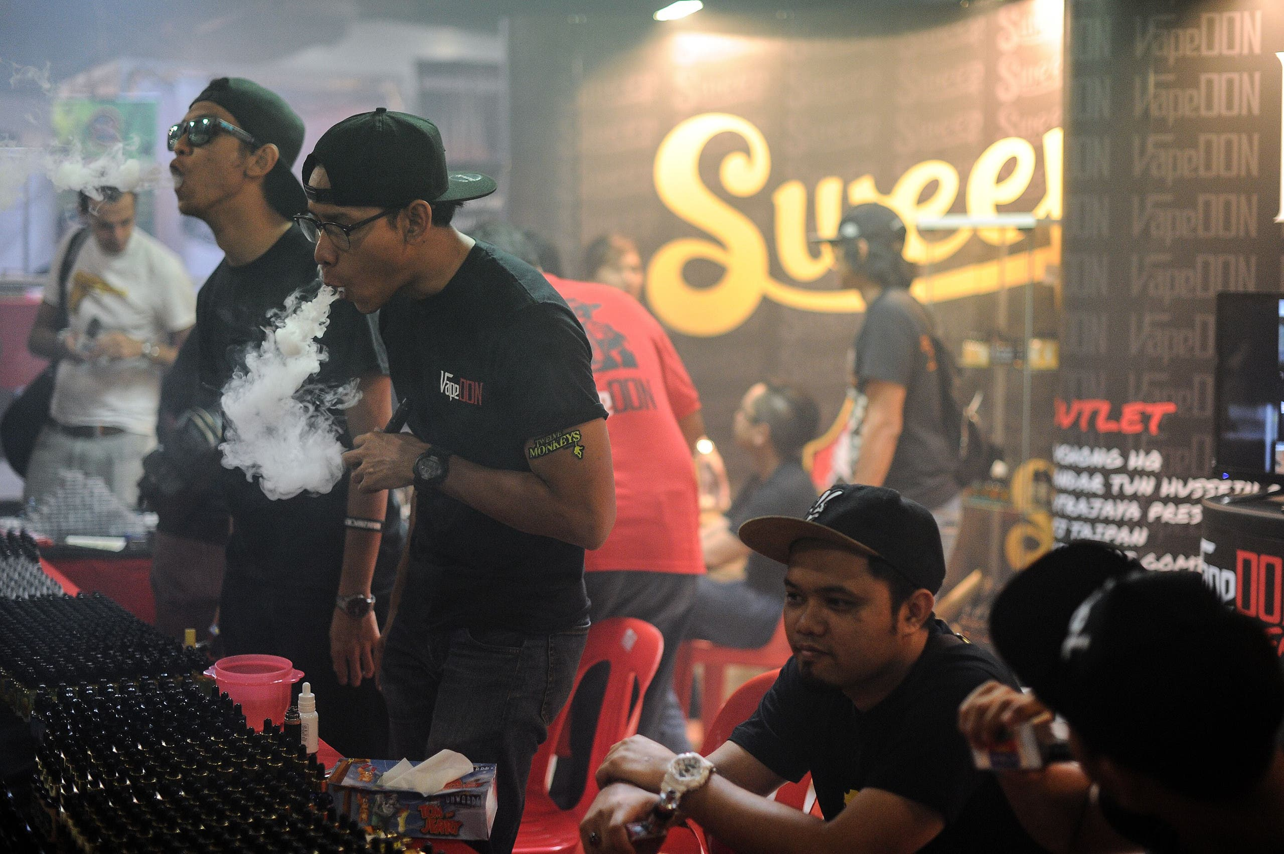 This picture taken on December 5, 2015 shows promoters smoking electronic cigarettes during the Vape Fair in Kuala Lumpur. afp