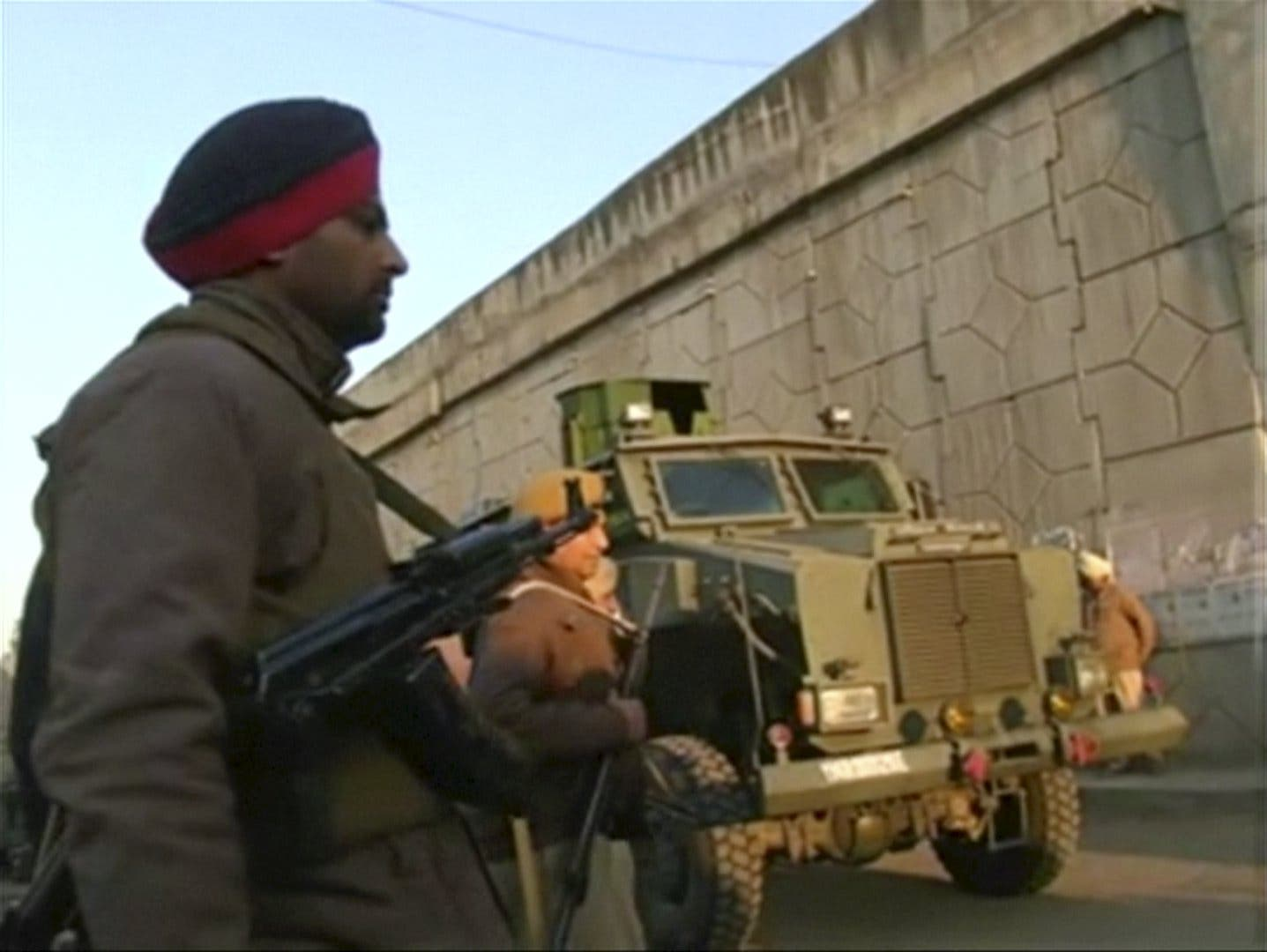 Police personnel stand guard following what officials said was an attack on an Indian Air Force base in Pathankot on Saturday near the border with Pakistan, in Pathankot, Punjab state, India, in this still frame taken from video, January 2, 2016. reuters