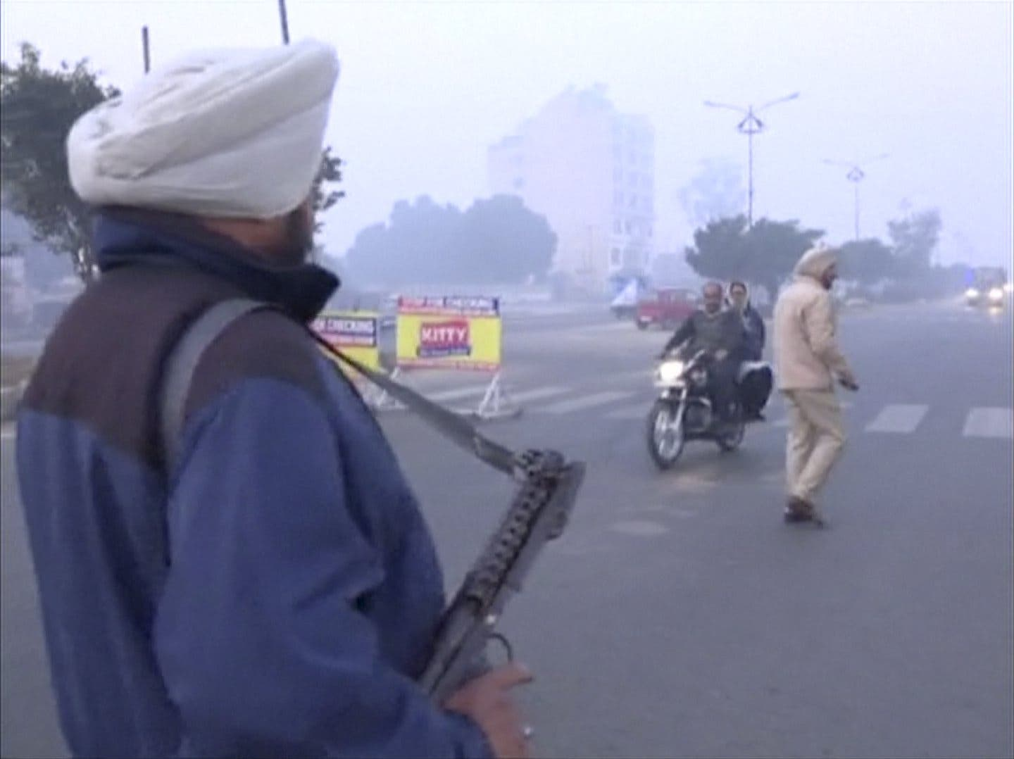 A policeman stands guard with a gun as vehicles pass by, following what officials said was an attack on an Indian Air Force base in Pathankot on Saturday, near the border with Pakistan, in Ludhiana, Punjab state, India, in this still frame taken from video, January 2, 2016. reuters