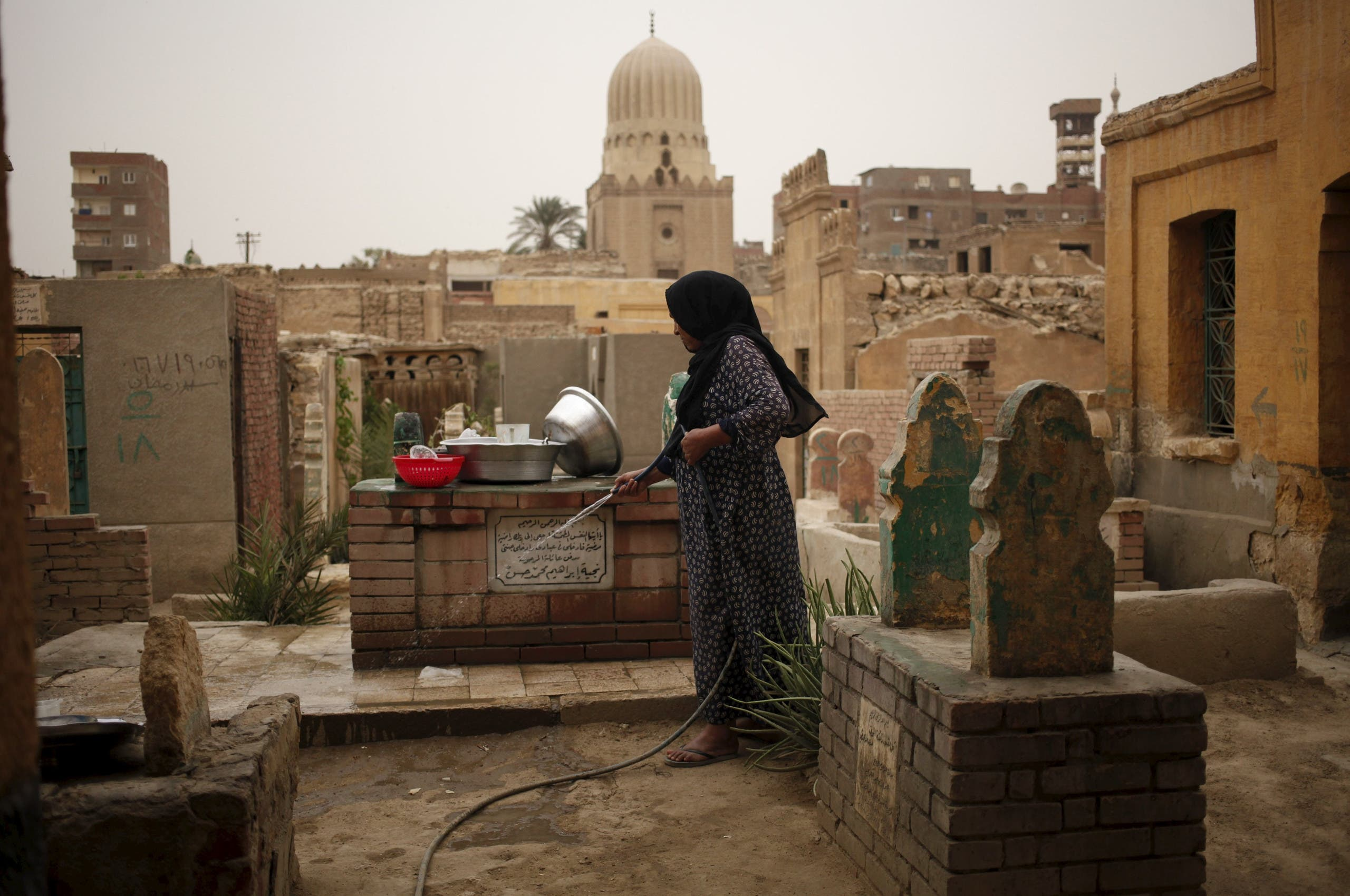 A woman who lives in the Cairo Necropolis cleans a tomb, outside her home in Cairo, Egypt, October 23, 2015.