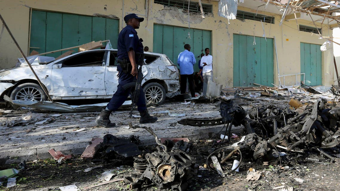 A Somali policeman walks past a damaged car at the scene of the blast near Al Kowsar supermarket in capital Mogadishu December 19, 2015.