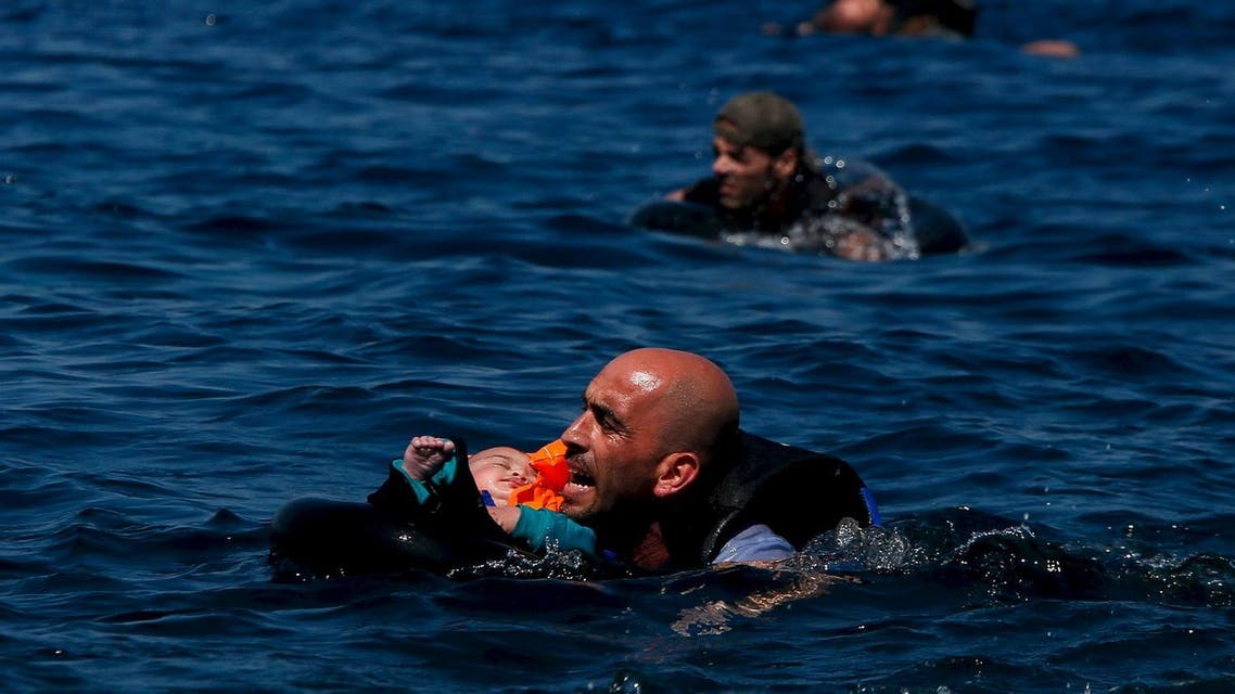 A Syrian refugee holding a baby swims towards the Greek island of Lesbos, September 12, 2015. (Reuters)