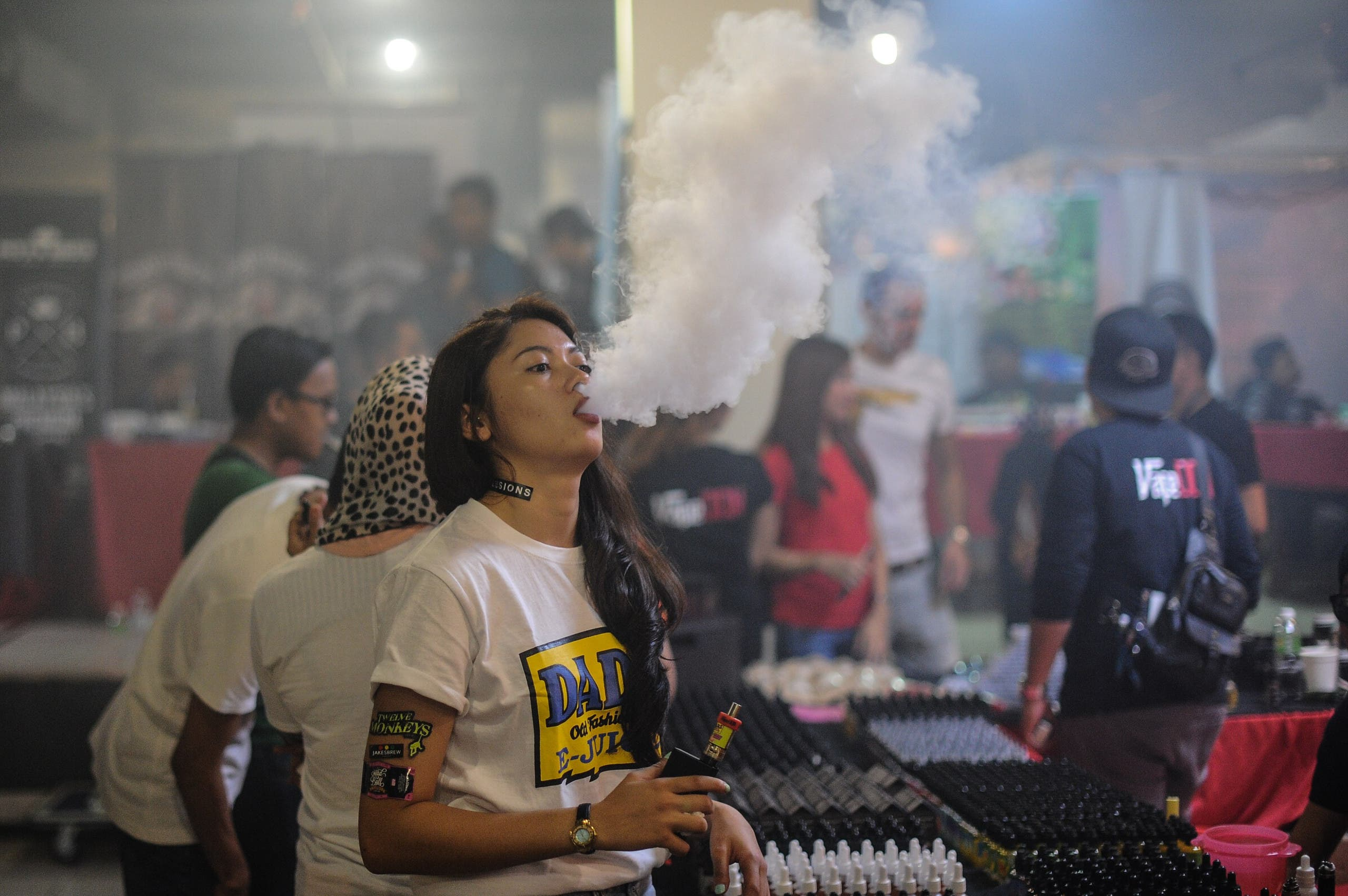 This picture taken on December 5, 2015 shows a promoter (C) smoking an electronic cigarette during the Vape Fair in Kuala Lumpur. afp