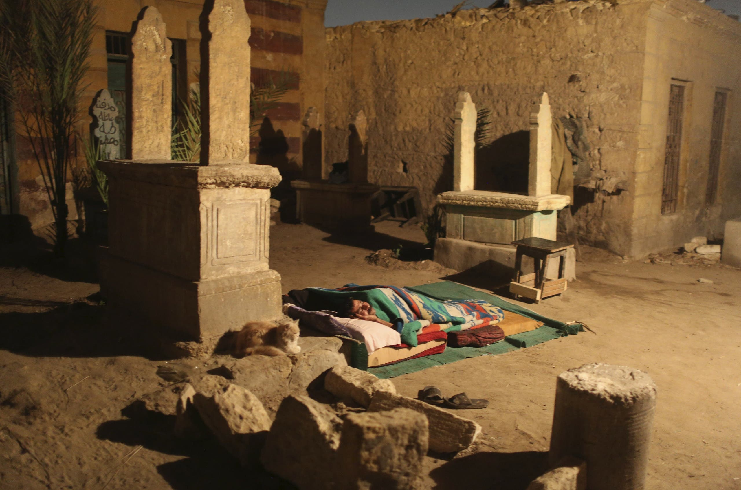 A man sleeps between tombstones in front of his single-room home on a hot night in the Cairo Necropolis, Egypt, October 13, 2015. reuters