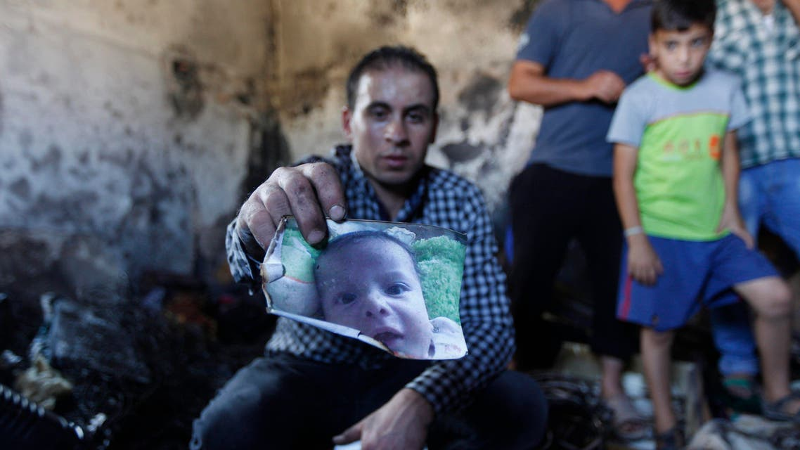 A relative holds up a photo of a one-and-a-half year old boy, Ali Dawabsheh, in a house that had been torched in a suspected attack by Jewish settlers in Duma village near the West Bank city of Nablus, Friday, July 31, 2015. AP