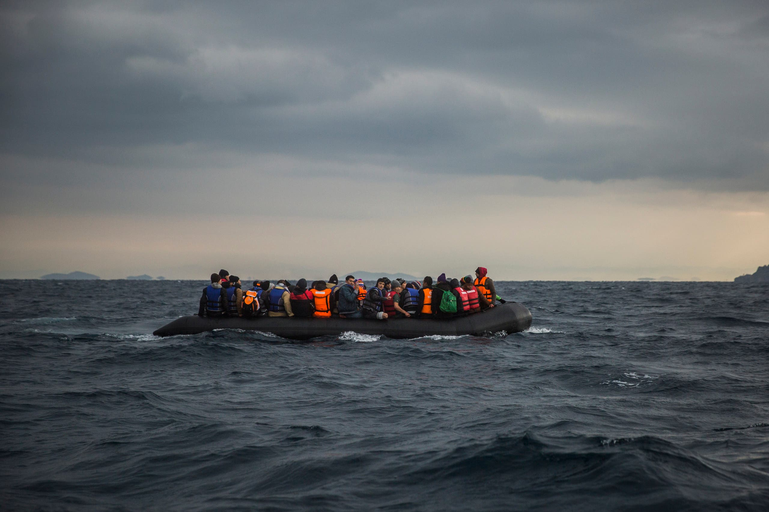 A file photo shows refugees and migrants onboard a dinghy approach the Greek island of Lesbos, after crossing the Aegean sea from Turkey. (AP/Santi Palacios)
