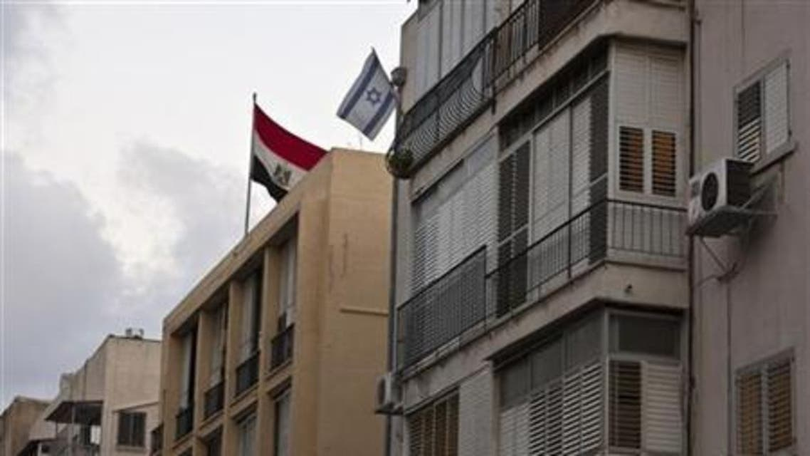 The Egyptian flag on the roof of the Egypt embassy in Tel Aviv, next to an Israeli flag from a nearby resident's balcony, August 20, 2011.