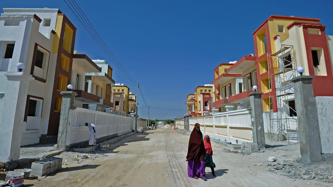 1832 - Mogadishu : People walk through Daru Salaam city, a new housing estate built amid an ecomonic boom, north Mogadishu on December 11, 2015. Somalia's elegant colonial villas were left in ruins by two decades of street fighting between warlords, and the seaside capital Mogadishu was dubbed the most dangerous city in the world. But now new housing estates are being built amid an economic boom as diaspora Somalis return and newly wealthy businessmen capitalise on the relative peace in the city.