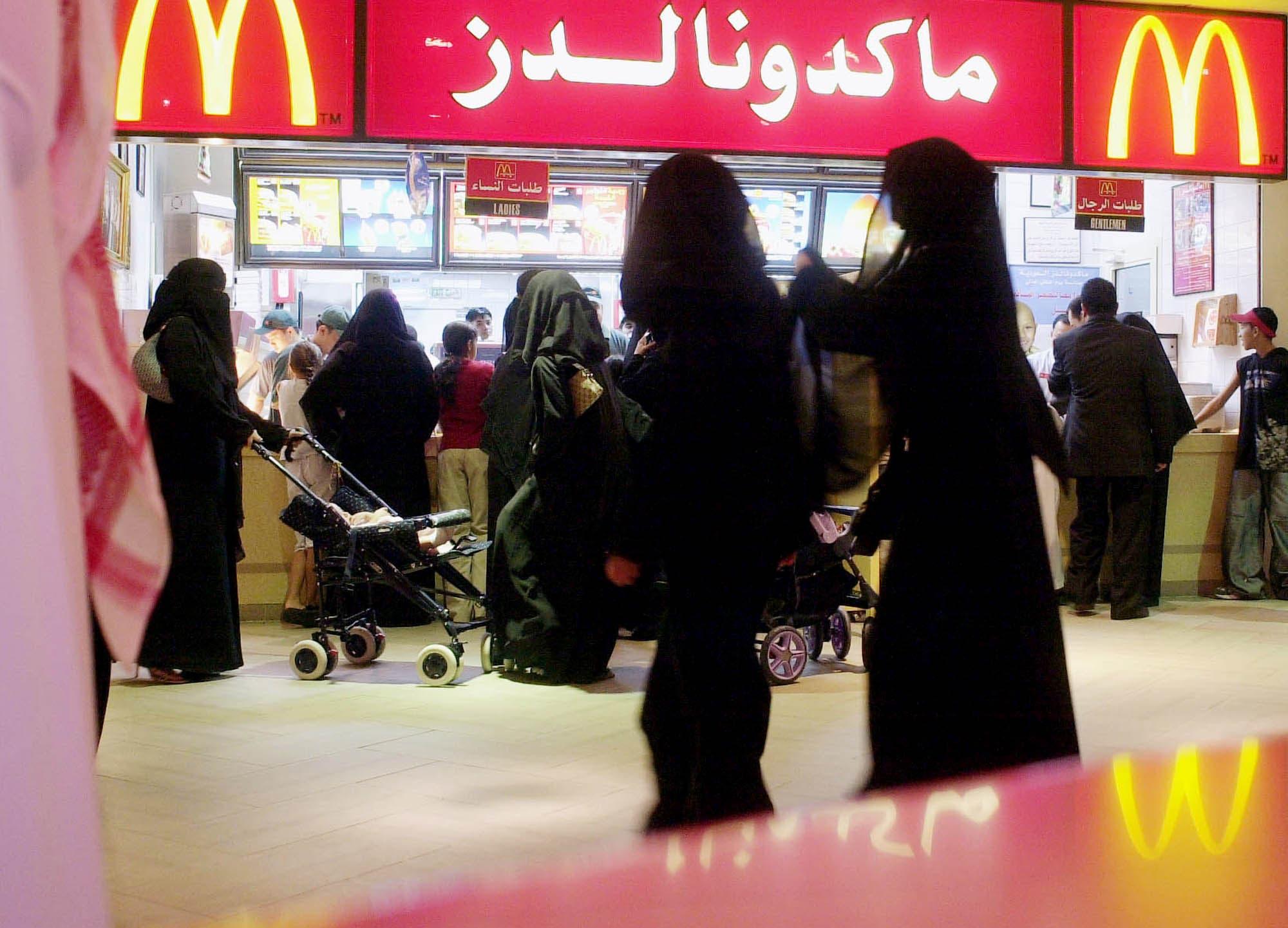 Saudis gather by a McDonalds fast food restaurant in a Riyadh, Saudi Arabia