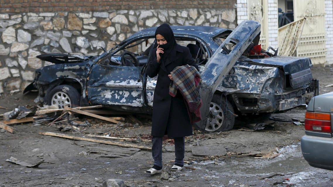 An Afghan woman walks past a damaged car after a suicide attack on a French restaurant in Kabul, Afghanistan January 2, 2016. (Reuters)