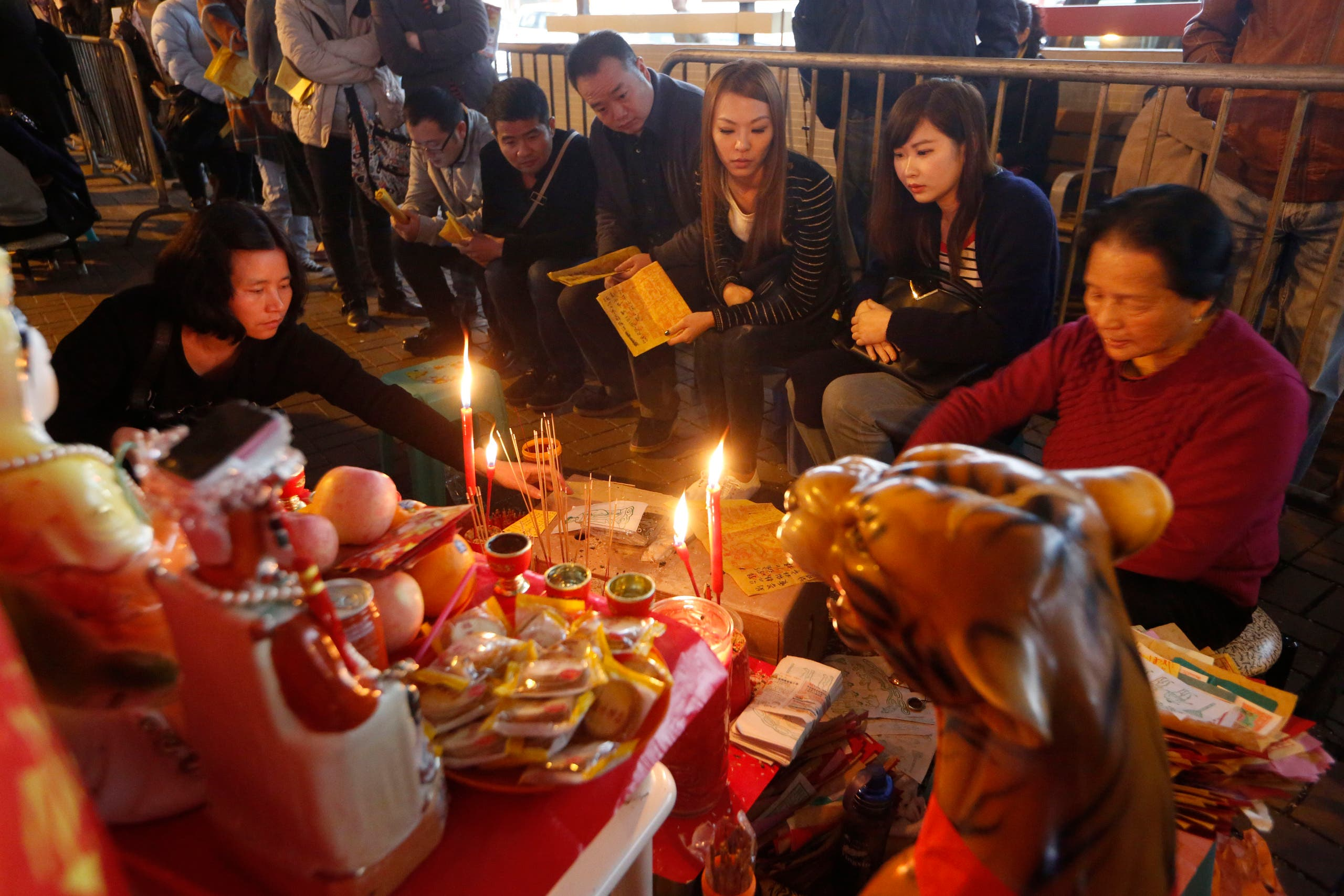 Believers wait at a stall for villain hitting in Hong Kong, Thursday, March 6, 2014. AP