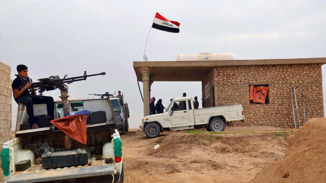 In this Friday, Oct. 17, 2014 photo, Iraqi security forces and tribal fighters gather to defend the city of Haditha 240 kilometers (150 miles) northwest of Baghdad, Iraq. Iraq is facing its worst crisis since the 2011 withdrawal of U.S. troops, with the Islamic State extremist group in control of about a third of the country. (AP Photo)