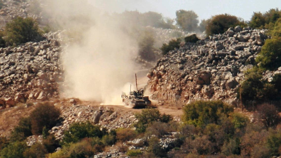 An Israeli army tank patrols during an investigation by the U.N. peacekeepers and Lebanese army soldiers near the site where Hezbollah attacked on Tuesday an Israeli patrol, in the hills of Kfar Shouba village, near the Israeli-occupied Shebaa farms, southern Lebanon, on Wednesday Oct. 8, 2014. Israel fired toward Hezbollah positions in southern Lebanon on Tuesday after the Shiite guerrillas set off an explosion along the tense border that wounded at least two Israeli soldiers, in the most serious incident between the two countries in months. Hezbollah issued a statement on the group's Al Manar TV station claiming responsibility for the blast in Shebaa on Tuesday, saying it targeted an Israeli patrol. (AP Photo/Lutfallah Daher)