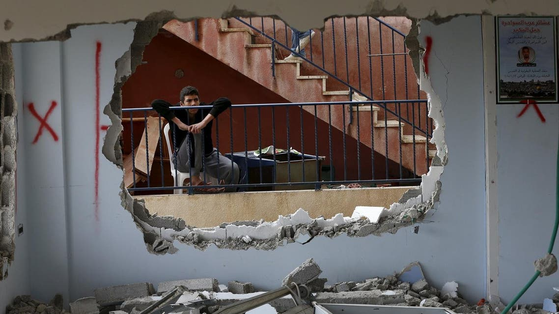 A relative looks at the demolished house of Palestinian Allyan in Jabel Mukaber. (Reuters)