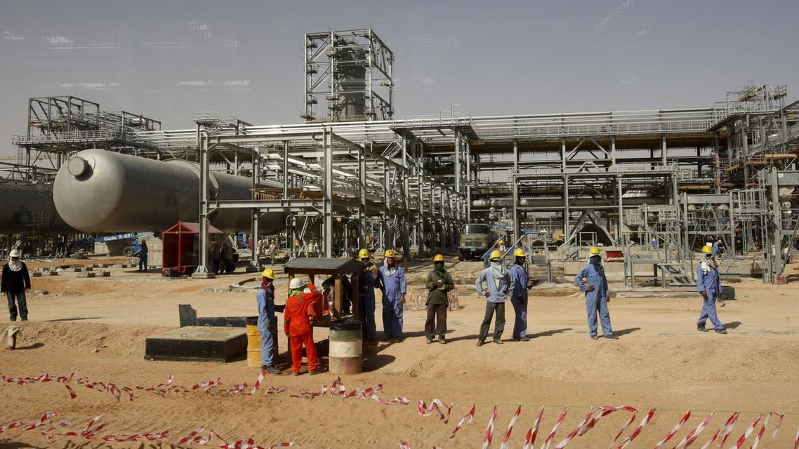 Workers look at journalists during a media tour of the Khurais oilfield, about 160 km (99 miles) from Riyadh, in this June 23, 2008 file photo reuters