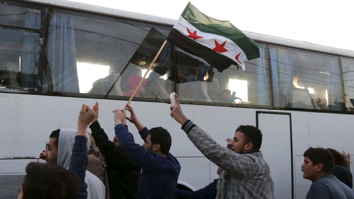 People cheer as a man waves a Syrian opposition flag upon the arrival of a convoy carrying more than 125 fighters from the besieged rebel-held Syrian town of Zabadani at the Masnaa border crossing between Lebanon and Syria, December 28, 2015.  (Reuters)