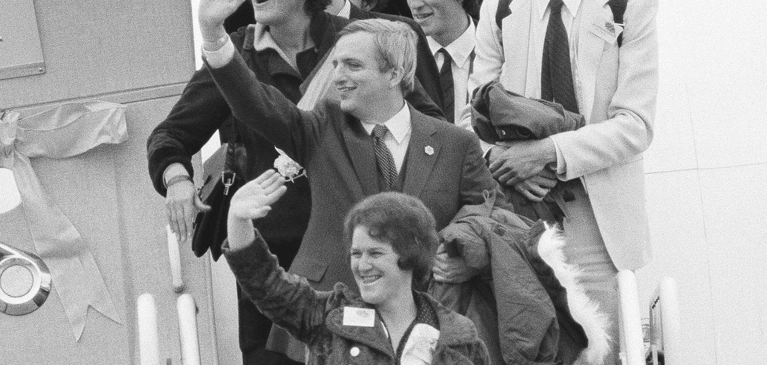 Freed hostage Moorhead Kennedy waves from the top of the steps as the Americans held hostage by Iran arrive at Andrews Air Force Base, Md., on Jan. 27, 1981. (AP)
