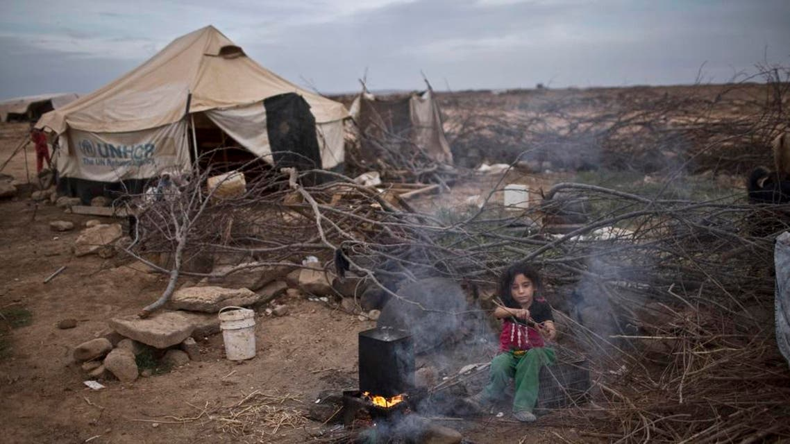 """In this Oct. 23, 2015 file photo, Syrian refugee Aysha Elwan, 5, helps her mother in breaking wood to be added under a fire to boil water outside her family's tent at an informal tented settlement near the Syrian border on the outskirts of Mafraq, Jordan. The number of Syrian refugees stranded in a remote desert area known as """"the berm,"""" on the Jordanian border has tripled to 12,000 since last month, the U.N. refugee agency said Tuesday, Dec. 8, 2015. (AP Photo/Muhammed Muheisen, File)"""