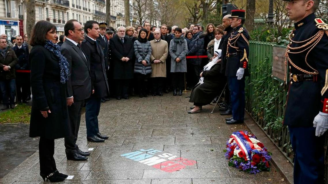 French President Francois Hollande (2ndL), Paris Mayor Anne Hidalgo (L) and Prime Minister Manuel Valls look at a commemorative plaque during a ceremony at the site where a policeman was killed during the last year's January attack in Paris, France, January 5, 2016. (Reuters)