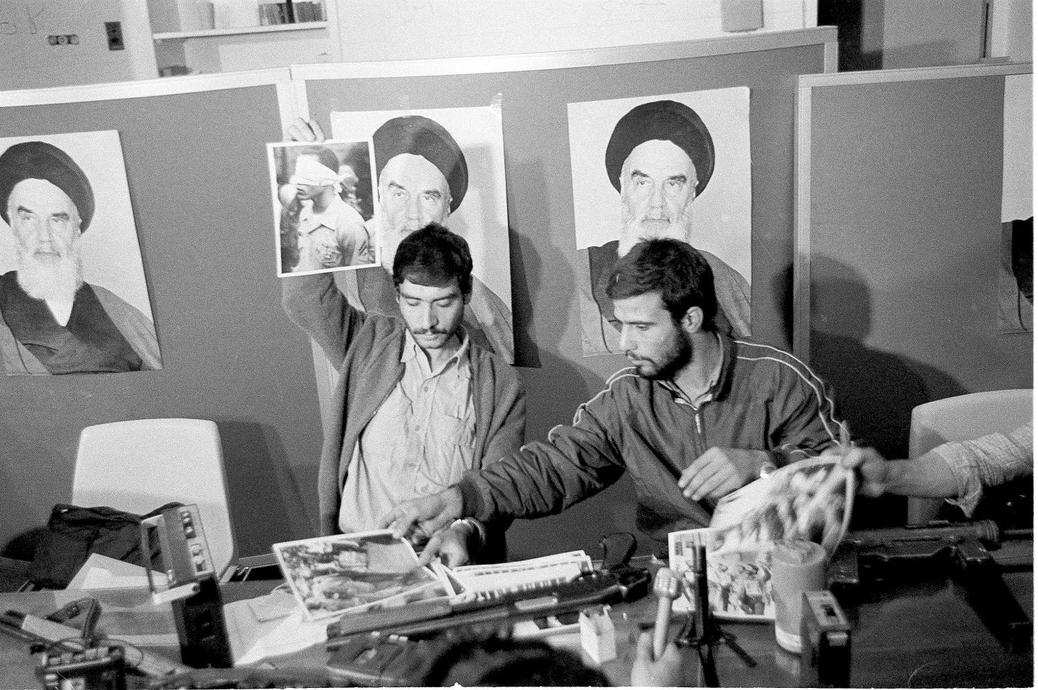 A representative of the Iranian students holds up a portrait of one of the blindfolded hostages, during a press conference in the U.S. Embassy in Tehran, Nov. 5, 1979. (AP)