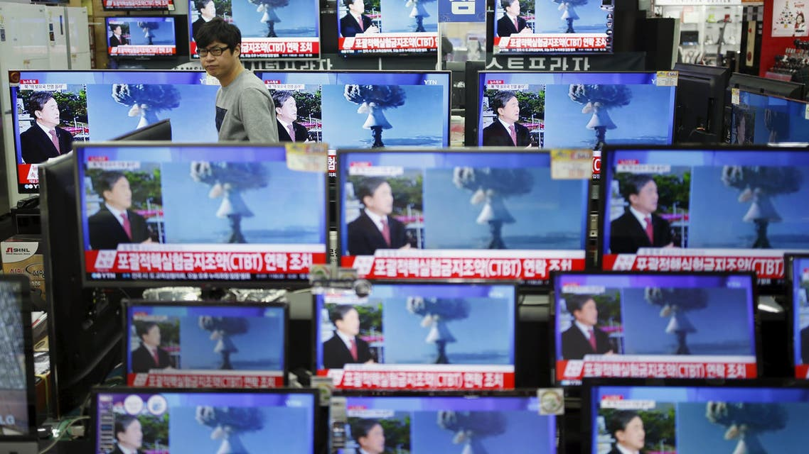 A sales assistant watches TV sets broadcasting a news report on North Korea's nuclear test, in Seoul. (Reuters)