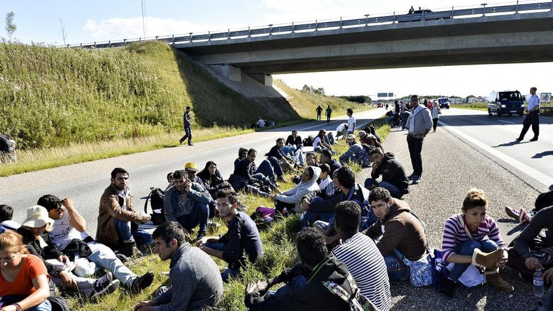 A group of refugees and migrants who were walking north sit down on the highway in southern Denmark on Wednesday, Sept. 9, 2015. The migrants have crossed the border from Germany, and after staying at a local school, they say they are now making their way to Sweden, to seek asylum. (Ernst van Norde/Polfoto via AP)