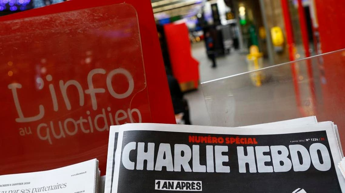 """A special edition of the satirical newspaper Charlie Hebdo that marks one year after, """"1 an apres"""" the attacks on it, on a newsstand Wednesday, Jan. 6, 2016 at a train station in Paris. Seventeen people died in the attacks on Charlie Hebdo on Jan. 7, 2015, and a kosher supermarket two days later. All three attackers died. (AP Photo/Francois Mori)"""