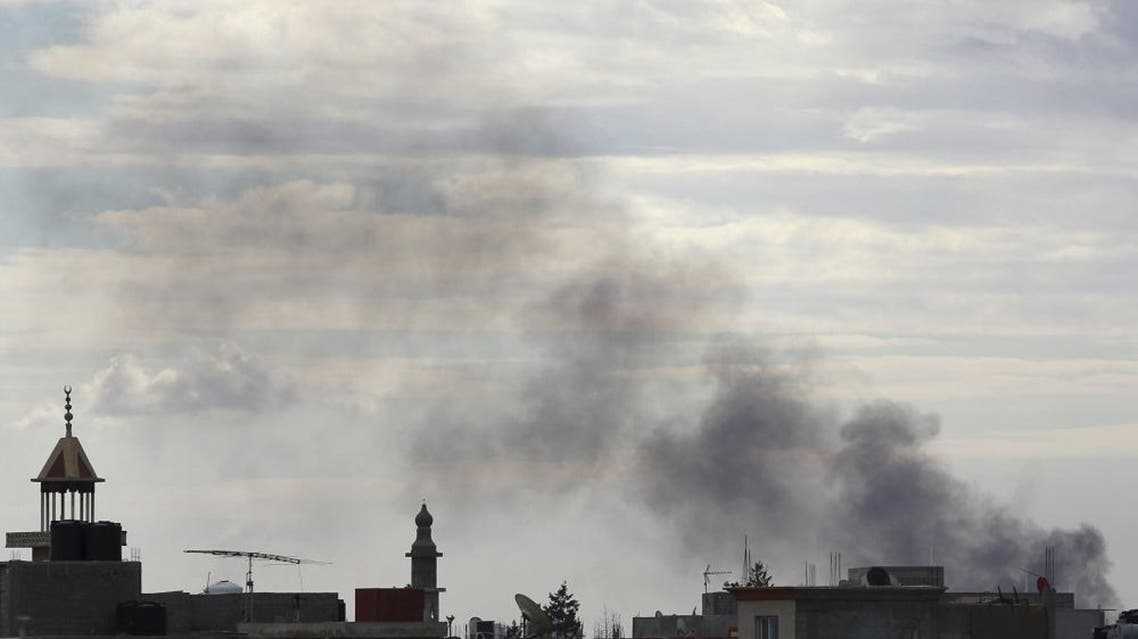 Black smoke billows in the sky above areas where clashes are taking place between pro