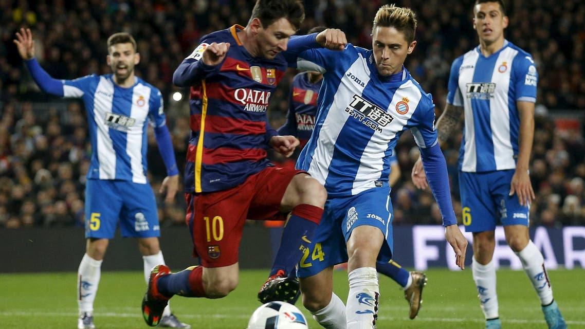 Lionel Messi (L) eludes Espanyol's Antonio Raillo. REUTERS