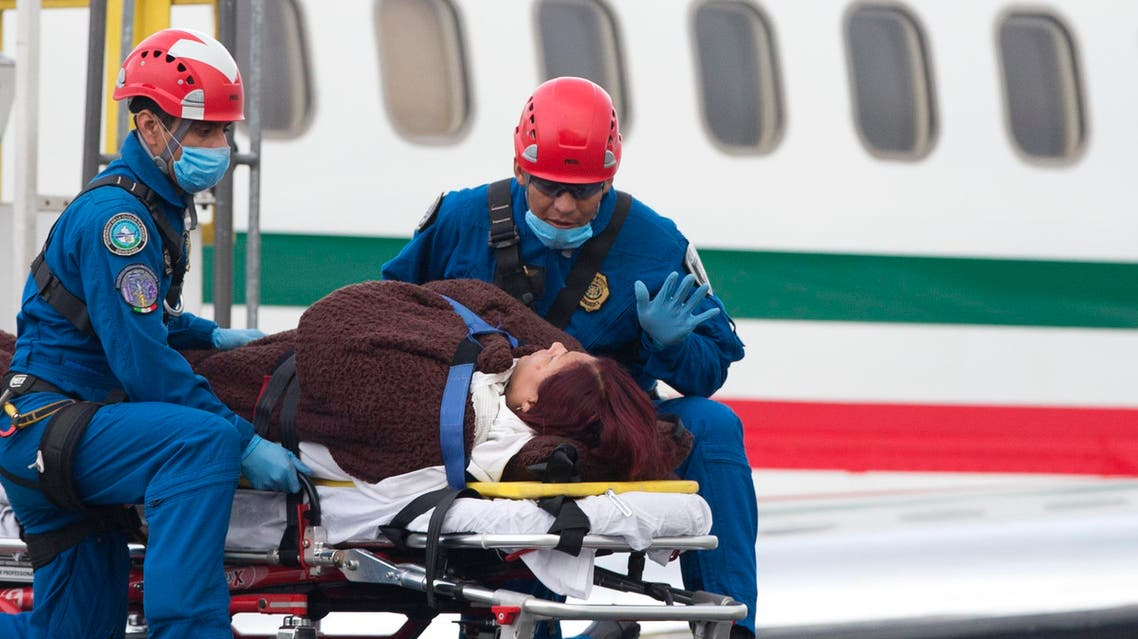 A paramedic talks to an injured woman as she is lowered from a plane carrying six Mexicans who were wounded in an attack by the Egyptian army, in Mexico City, Friday, Sept. 18, 2015. (AP)