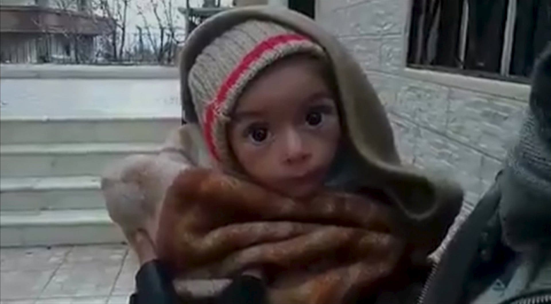 A toddler is held up to the camera in this still image taken from video said to be shot in Madaya on January 5, 2016. (Reuters)